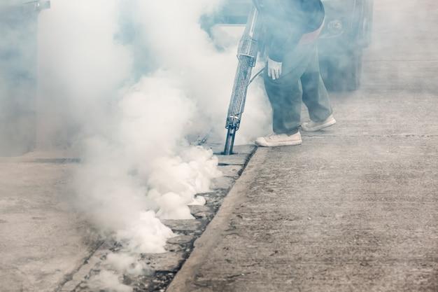 Рабочий затуманивает уличную канализацию инсектицидами, чтобы убить место размножения комаров aedes, переносчика денге и вируса зика