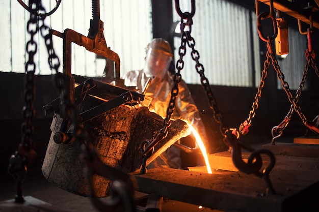 Worker in foundry pouring hot metal into mold.