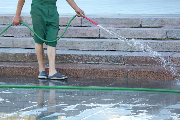 Рабочий из шланга поливает улицу города