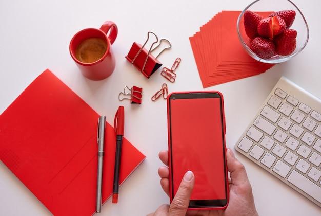 Рабочий дома отдыхает с кофе и клубникой, разговаривает по телефону с красным экраном. белый рабочий стол и красные аксессуары