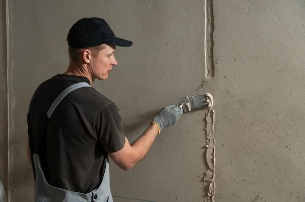 Рабочий получает штукатурку на стене