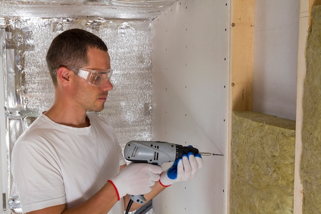 Worker in goggles with screwdriver working on insulation. drywall on wall beams, insulating rock wool staff in wooden frame.