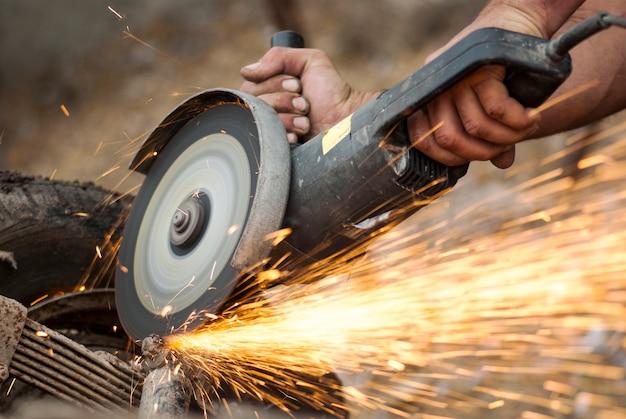 그라인더 기계와 불꽃으로 금속 시트를 절단하는 작업자.
