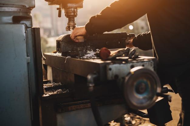 労働者は産業ワークショップで万力ツールでプラスチック部品を研削します。
