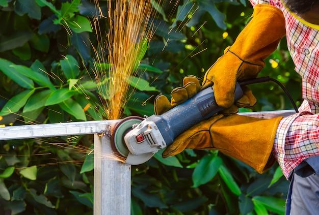 ハンドヘルドアングルグラインダーで鉄骨を研削する労働者。火花が飛んで研削
