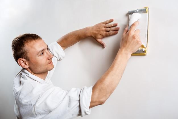 Работник, шлифовка белой стене наждачной бумагой.