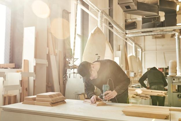 Рабочий шлифует древесину углового шлифовального станка на своем рабочем месте