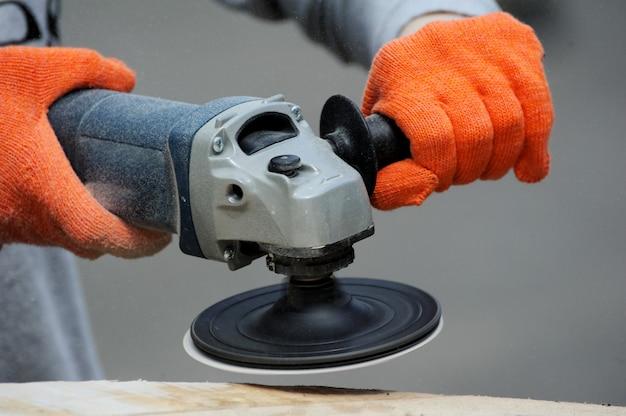 Рабочий шлифует древесину углового шлифовального станка