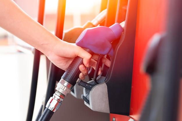 주유소의 작업자 손은 자동차 엔진 가솔린을 채우기 위해 연료 디스펜서에서 연료 노즐을 처리합니다.
