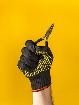 Worker hand in glove holds diagonal pliers on a yellow background. idea for building or renovation