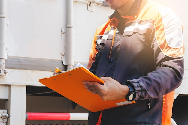 Worker hand holding clipboard inspecting details shipment to transport