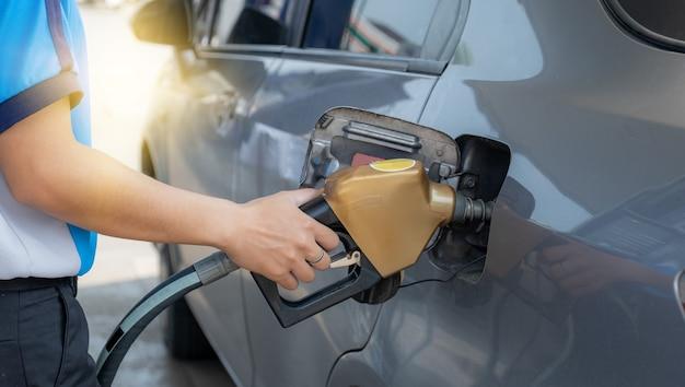 급유를 위해 자동차 탱크의 오일 펌프에서 황금 노즐 펌프 건 휘발유를 들고 있는 작업자.