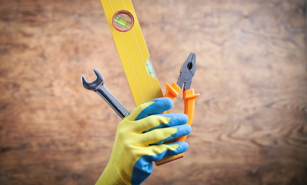 Worker hand holding level, wrench, pliers. working tools