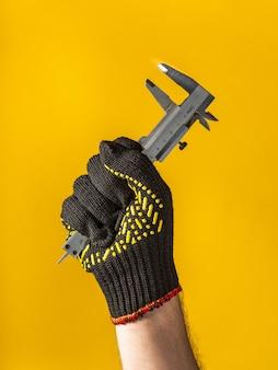 手袋をはめた労働者の手は、黄色の背景にキャリパーを保持します。建物や改修のアイデア