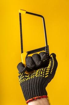 手袋をはめた労働者の手は、黄色の背景にのこぎりまたは弓のこを保持します。建物や改修のアイデア
