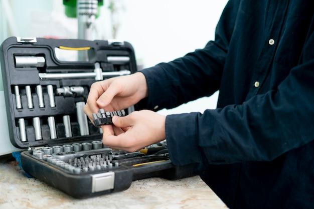 Рука рабочего берет инструмент из набора, чтобы сделать проект