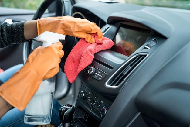 Covid-19 예방을 위한 작업자 손 착용 장갑 청소 차 내부. 위생의 개념