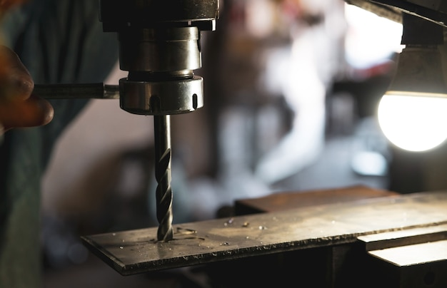 Worker hand working on milling machine to change metal drill bit tool for drilling metal