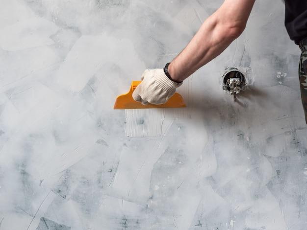 흰색 퍼티와 주걱을 들고 작업자 손. 집에서 수리 및 개조. 새로운 인테리어 디자인.