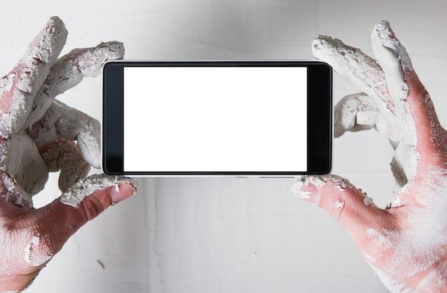 Руки работника в белой штукатурке со смартфоном фотографируют штукатурную стену, плоскую планировку. до неузнаваемости человек с пустым экраном телефона, пов.