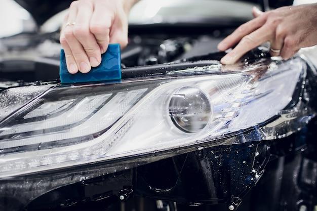 Рабочие руки устанавливают автомобильную краску, защитную пленку, пленку, автоматическое включение фар
