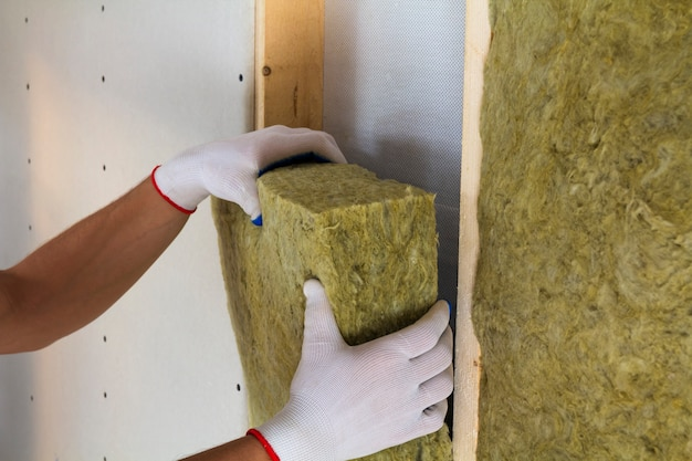 Worker hands in white gloves insulating rock wool