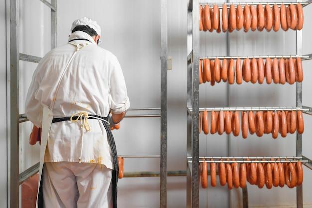 Рабочий вешает сырые колбасы на стеллажи в складском помещении на мясоперерабатывающем заводе