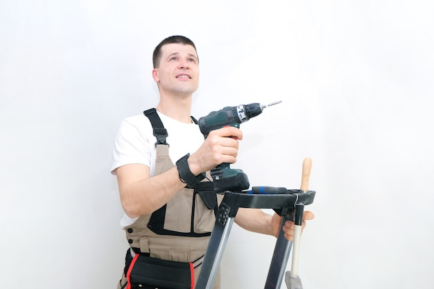 Рабочий с отверткой в руках. техник в специализированной спецодежде