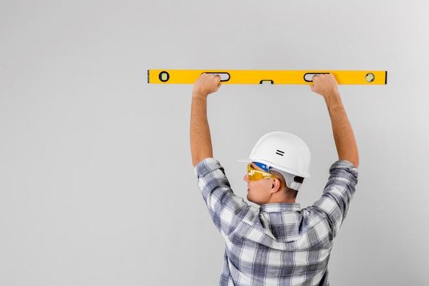 Работник держит уровень духа на стене