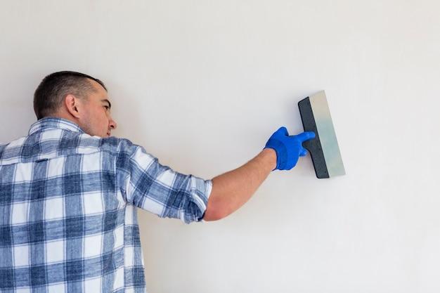 Рабочий держит шпатель на стене