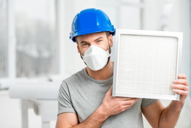 Рабочий держит воздушный фильтр для установки в системе вентиляции дома. концепция чистоты воздуха
