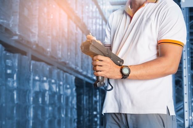 Работник, держащий сканер штрих-кода на складе, складской инвентарь и управление
