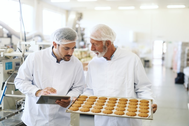 Worker holding casserole with cookies while supervisor checking quality and holding tablet. food factory interior.