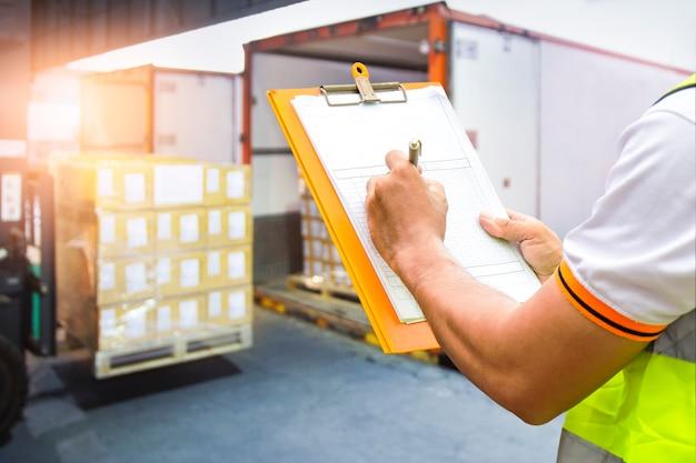 Рабочий, держащий буфер обмена, контролирует загрузку упаковочной коробки в грузовой контейнер складской логистики