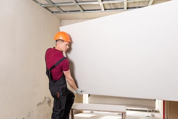 Рабочий держит гипсокартон для крепления к потолку