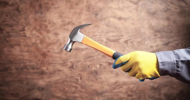 Рабочий, держащий молоток. строительный инструмент