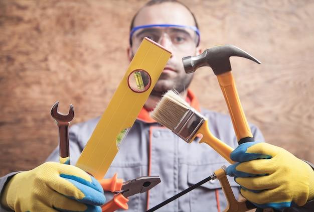 ハンマー、のこぎり、ブラシ、レベル、レンチ、ペンチを持っている労働者。作業ツール