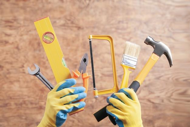 망치, 톱, 브러시, 레벨, 렌치, 펜치를 들고 노동자. 작업 도구