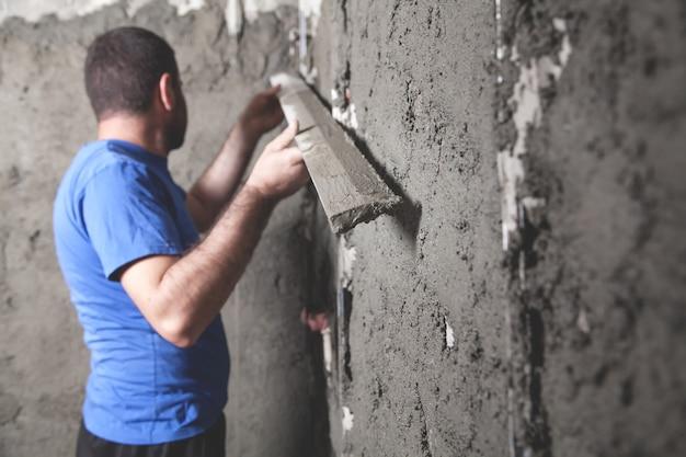 レベルツールを保持している労働者。しっくいの壁。