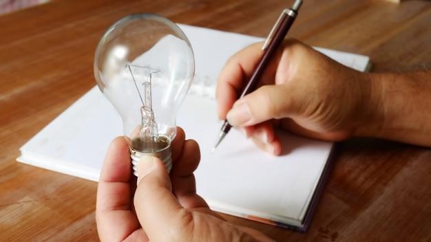 왼손에 전구를 들고 오른손을 사용하여 좋은 아이디어를 기록하는 작업자