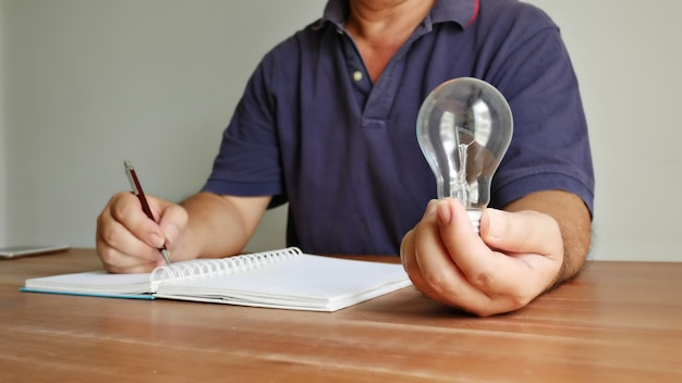 Worker holding light bulb in left hand and using right hand recoarding the good idea