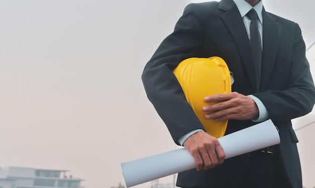 Worker holding safety hard hat with blueprint