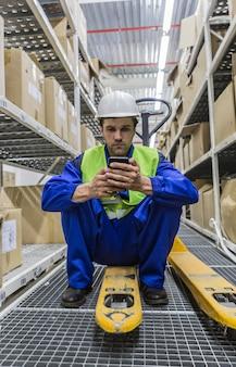 Рабочий, держащий смартфон в каске и униформе, сидит на тележке с поддонами на складе.