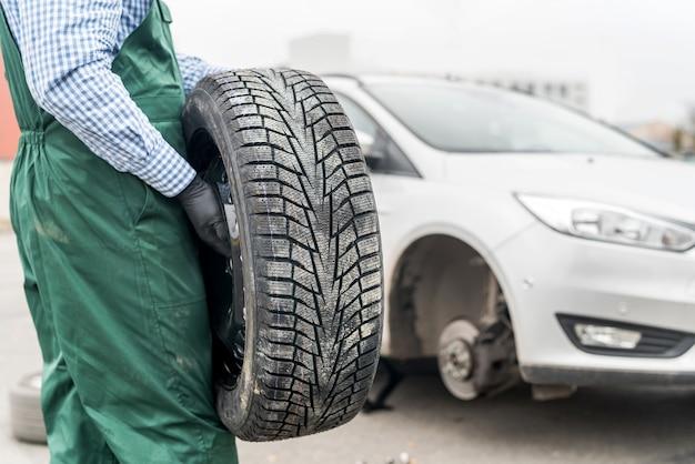 Рабочий держит запасное колесо на сломанной машине