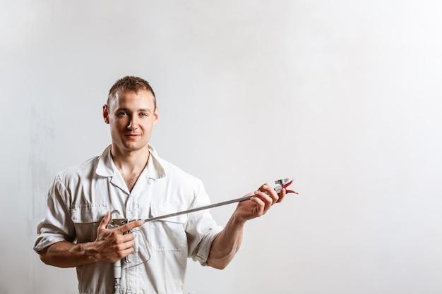 Работник держа оружие брызга на белой стене.
