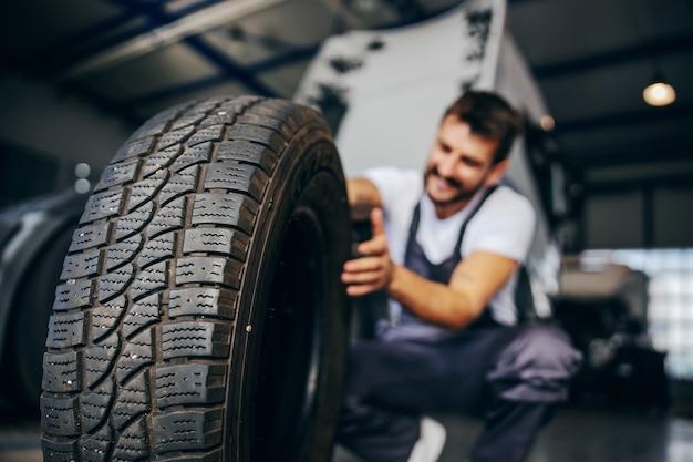 タイヤを持っている労働者と彼はそれを変えたいと思っています。背景にはトラックがあります。タイヤにセレクティブフォーカス。