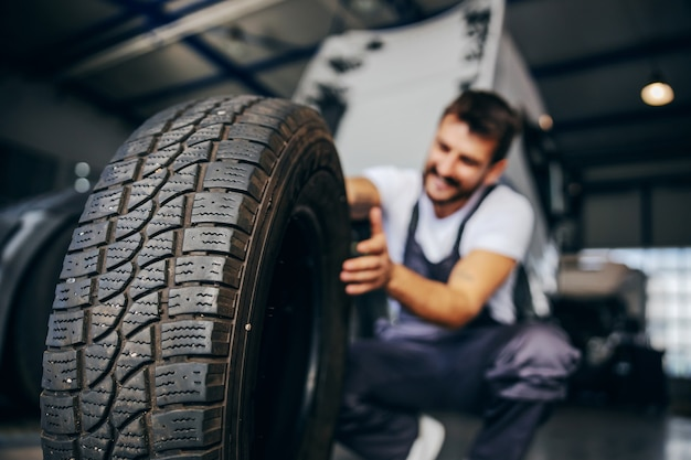 Worker holding tire and he wants to change it. in background is truck. selective focus on tire.