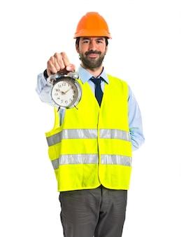 Worker holding vintage clock