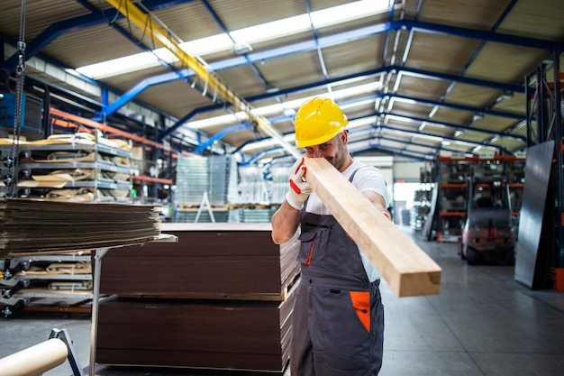 Worker holding wood plank and working in furniture factory or wood processing industry
