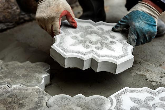労働者はコンクリート舗装タイルを持っています。形作られた装飾的な舗装スラブを敷設する作業の概念。